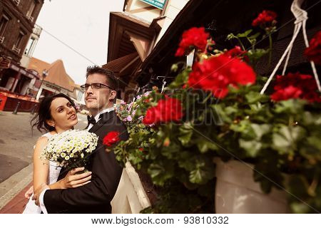Bride And Groom In The City Near A Flowerpot