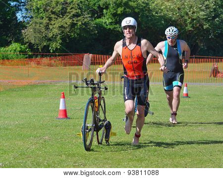 Triathlon Men running in to change over with bikes.