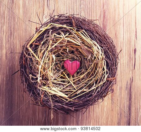 red heart with nest on old shabby wooden background