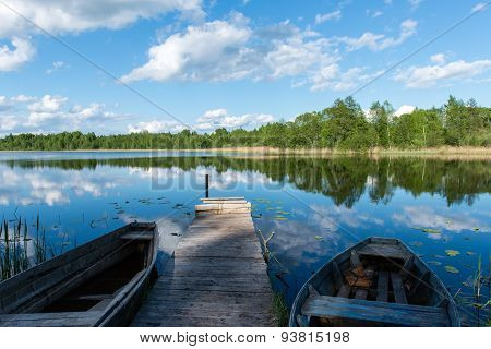 White Clouds On The Blue Sky Over Blue Lake With Boats And Boardwalk