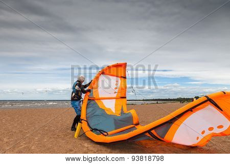 Kite Surfer  Is Preparing His Kite On A Windy Cold Day