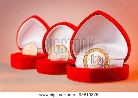 Red Gift Boxes With One Euro, Ten Roubles And One Cent Coins. Focus On Rouble Coin