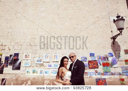 Bride And Groom Against A Wall Full Of Paintings