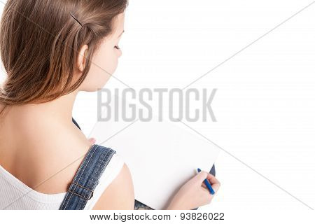 Young woman drawing in her note pad. Back view