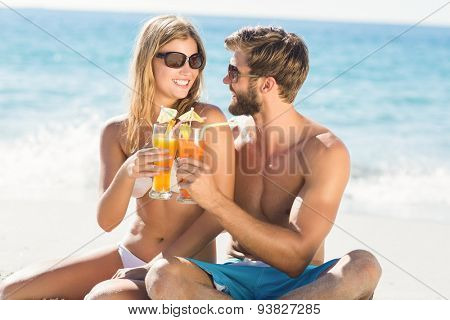 happy couple drinking a cocktail at the beach