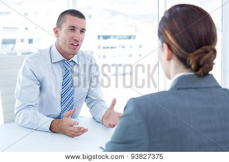 Businessman conducting an interview with businesswoman in an office