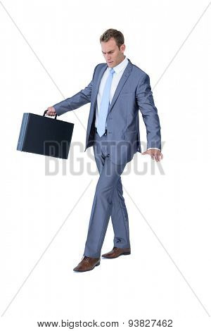 Businessman walking in equilibrium with suitcase on white background