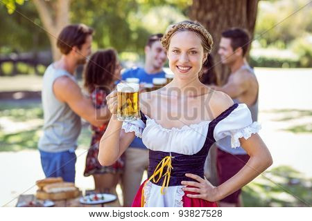 Pretty oktoberfest blonde toasting in the park on a sunny day
