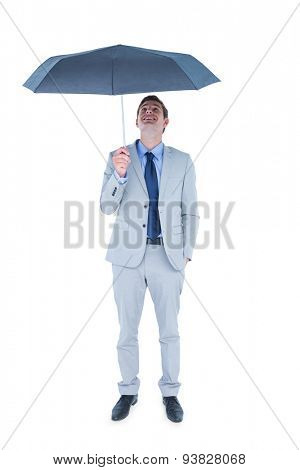 Businessman sheltering under umbrella on white background