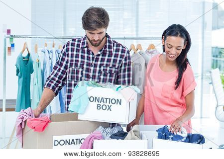 Portrait of smiling young friends volunteers separating clothes