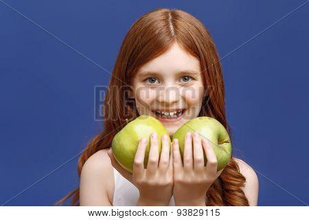 Smiling girl holding apples