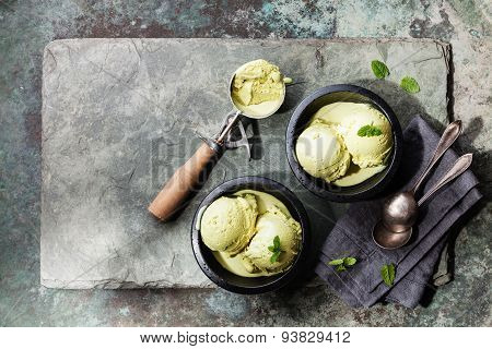 Green Tea Ice Cream With Mint Leaves And Spoon For Ice Cream On Stone Slate Background