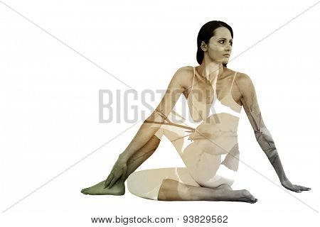 Fit woman doing the half spinal twist pose in fitness studio against autumnal leaves against blurred plants