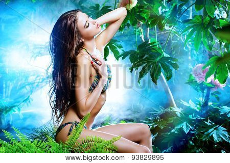 Beautiful sexy woman in bikini among tropical plants. Beauty, fashion. Spa, healthcare. Tropical vacation.