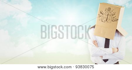 Anonymous businessman with arms crossed against blue sky