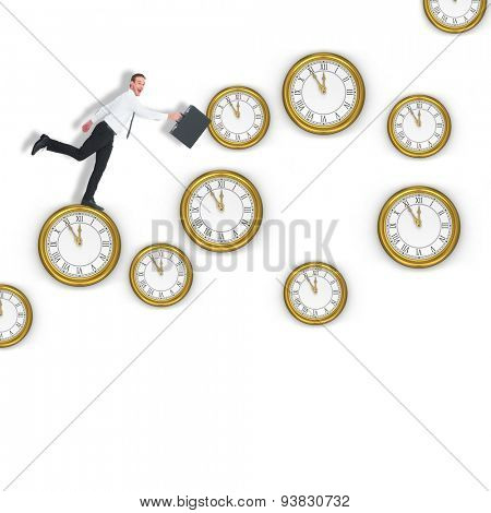 Happy businessman leaping with his briefcase against clocks