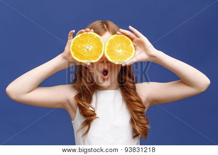Smiling girl holding halves of orange