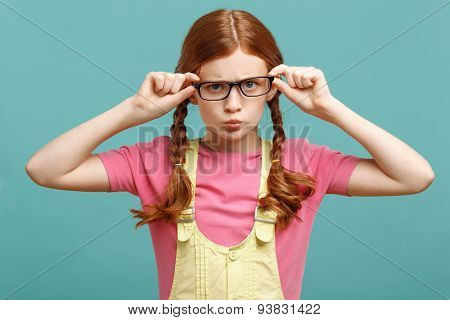 Little girl touching her glasses