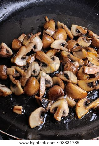 Fried Sliced Mushrooms In Butter In A Frying Pan