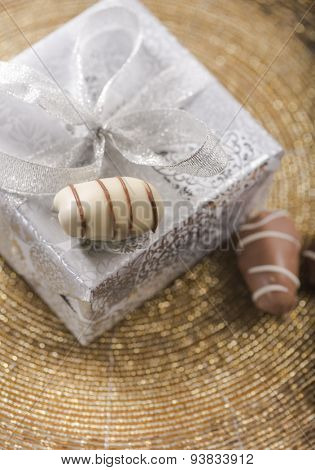 A wrapped gift box and date chocolates from top angle.