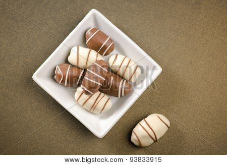 Date fruit chocolates. Top view of a white bowl with plenty of date chocolates..
