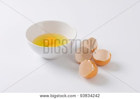 bowl of raw eggs and egg shells on white background