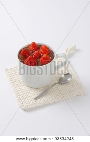 mug of strawberries in chocolate pudding on white table mat