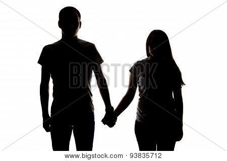 Silhouette of two teenagers holding hands