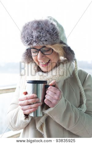 Cheerful woman in warm clothing holding insulated drink container