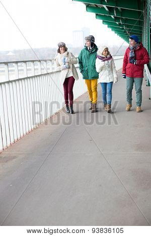 Multiethnic friends walking on footpath during winter