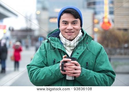 Portrait of man in winter clothing smiling on city street