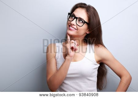 Healthy Young Thinking Woman In Glasses Looking Up On Blue Background