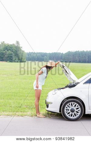 Side view of woman examining broken down car on country road
