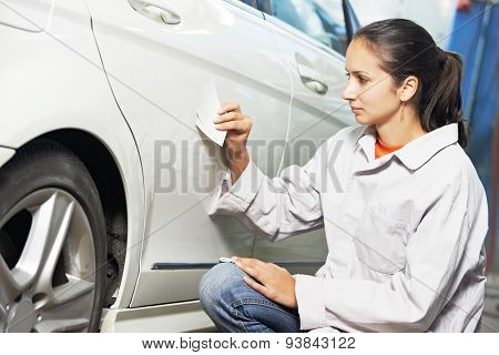 colourist woman matching paint of car element at automobile repair and renew service station with color example cards