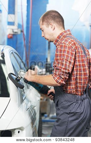 auto mechanic worker polishing car body at automobile repair and renew service station shop by power buffer machine