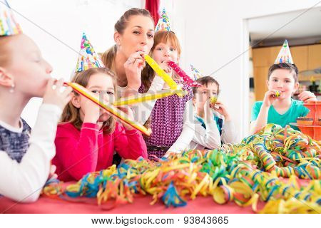 Children having birthday party with fun blowing streamers, group of kids with mother
