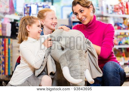 family in toy store cuddling with stuffed animal, mother with two daughters