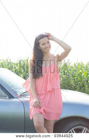 Portrait of happy woman leaning by convertible against clear sky