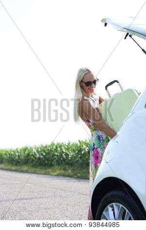 Happy woman loading suitcase in car trunk against clear sky