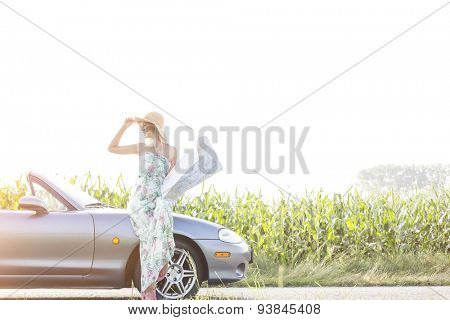 Happy woman holding map while standing by convertible on sunny day