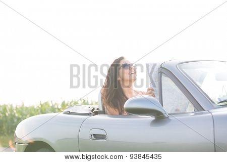 Happy woman holding map while sitting in convertible against clear sky