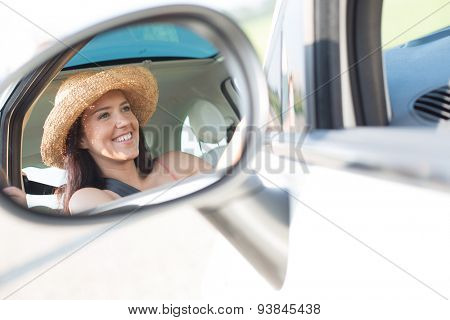 Reflection of happy woman in rearview mirror of car