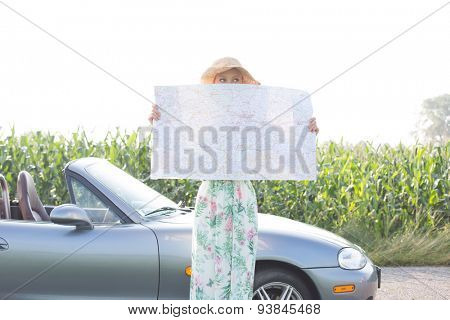 Woman hiding face with map by convertible against clear sky