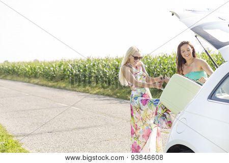 Happy women loading luggage in car trunk against clear sky