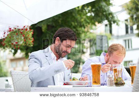Businessmen eating food at outdoor restaurant