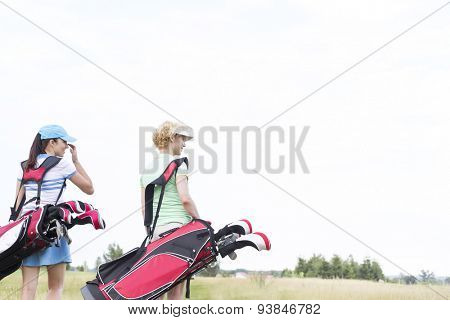 Rear view of women with golf club bags at course against clear sky