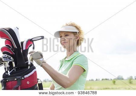 Female golfer with golf club bag against clear sky