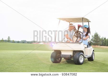 Couple looking at each other while sitting in golf cart against clear sky