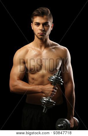 Muscle young man holding dumbbells on dark background