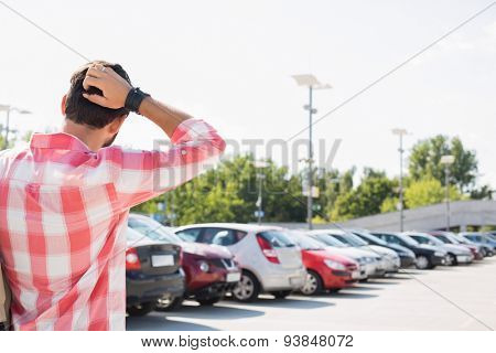 Rear view of man with hand behind head standing on city street against clear sky